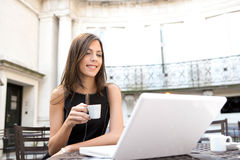 Businesswoman drinking coffee with laptop Stock Images
