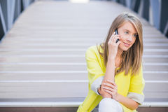 Young attractive businesswoman sitting on the stairs and using s stock photography