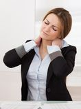 Young attractive businesswoman suffer from neck pain Stock Image