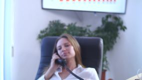 Young attractive businesswoman talking on telephone with her legs on the table in the office stock video