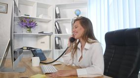 Young attractive businesswoman talking on telephone in the office and smiling stock video