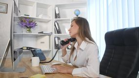 Young attractive businesswoman talking on telephone in the office and smiling Stock Photography