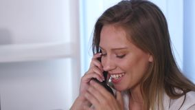 Young attractive businesswoman talking on telephone in the office and smiling. close up stock footage