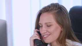 Young attractive businesswoman talking on telephone in the office and smiling. close up stock video footage