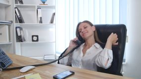 Young attractive businesswoman talking on telephone and using smartphone in the office and smiling stock footage