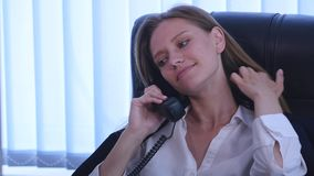 Young attractive businesswoman talking on telephone and using smartphone in the office and smiling stock video