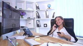 Young attractive businesswoman talking on telephone and using smartphone in the office and smiling royalty free stock photo