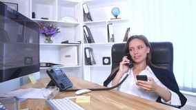Young attractive businesswoman talking on telephone and using smartphone in the office and smiling royalty free stock images