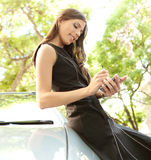 Businesswoman leaning on car with smartphone. Young attractive businesswoman using her smart phone while leaning on a car in a tree lined street, outdoors Stock Photography