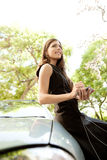 Businesswoman leaning on car with smartphone. Young attractive businesswoman using her smart phone while leaning on a car in a tree lined street, smiling Royalty Free Stock Photos