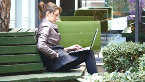 Young attractive businesswoman using laptop on a break outdoors. Young attractive businesswoman freelancer using laptop and answering mobile phone outdoors stock footage