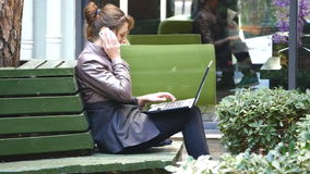 Young attractive businesswoman using laptop on a break outdoors. Young attractive businesswoman freelancer using laptop and answering mobile phone outdoors stock video footage