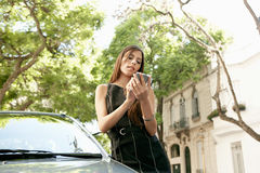 Businesswoman leaning on car with smartphone. Young attractive businesswoman using a smart phone while leaning on a shiny car in a classic business street Royalty Free Stock Photo