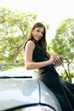Businesswoman leaning on car with smartphone. Stock Photo