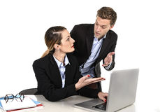 Young attractive businesswoman working at computer laptop in office arguing with work colleague in stress. Fighting against each other in front of computer Royalty Free Stock Photography