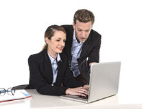 Young attractive businesswoman working at computer laptop in office talking with work colleague smiling relaxed Royalty Free Stock Image