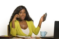 Young attractive and busy black afro American business woman working at home office computer desk talking on the phone holding cal. Culator accounting stressed stock images