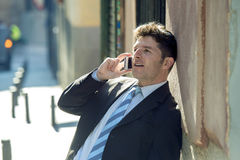 Young attractive and busy businessman with blue eyes wearing suit and tie talking business on mobile phone outdoors Royalty Free Stock Photos