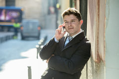 Young attractive and busy businessman with blue eyes wearing suit and tie talking business on mobile phone outdoors Stock Photos