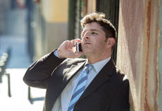 Young attractive and busy businessman with blue eyes wearing suit and tie talking business on mobile phone outdoors Stock Images