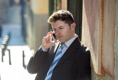 Young attractive and busy businessman with blue eyes wearing suit and tie talking business on mobile phone outdoors Stock Photography