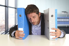 Young attractive busy businessman overwhelmed suffering crazy stress at office exhausted and helpless Royalty Free Stock Image