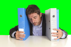 Young attractive busy businessman overwhelmed suffering crazy stress at office exhausted. Holding paperwork folders napping on desk   on green chroma key screen Royalty Free Stock Photo