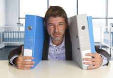 Young attractive busy businessman overwhelmed suffering crazy stress at office looking sad. And desperate holding paperwork folders on desk in business Stock Image