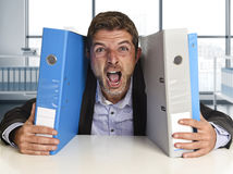 Young attractive busy businessman overwhelmed suffering crazy stress at office screaming desperate. Holding paperwork folders on desk in business frustration Royalty Free Stock Images