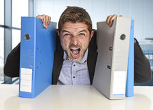 Young attractive busy businessman overwhelmed suffering crazy stress at office screaming desperate. Holding paperwork folders on desk in business frustration Royalty Free Stock Image