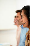 Young attractive callcenter people using earphone Stock Images