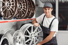 A young and attractive car mechanic is choosing a tire rim royalty free stock photos
