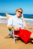 Young Attractive Casual Businessman Relaxing at the Beach Talkin Royalty Free Stock Photos