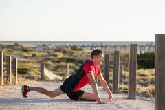 Young attractive Caucasian blond man on his 30s stretching leg i stock photo