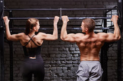 Young attractive caucasian crossfit man and woman working out in gym, rear view, couple