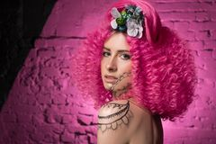 Young attractive caucasian girl model with african style curly bright pink hair, tattooed face and neck and flowers woven into her. Hair. Photo in the studio on royalty free stock photo