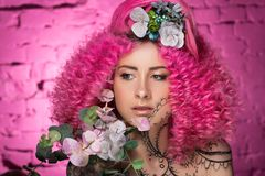 Young attractive caucasian girl model with curly bright pink hair, tattooed face and flowers woven into her hair. Photo in the. Young attractive caucasian girl royalty free stock photography