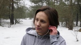 Young Attractive Caucasian girl puts in her earphones before running in the snowy park in winter. Close up front shot. Slow Motion.  stock footage