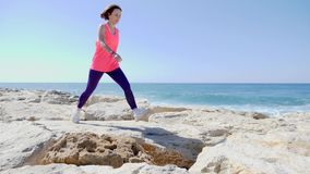 Young attractive caucasian girl running over the rocks near the sea. Waves hitting the rocky beach and water splashing stock video
