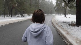 Young Attractive Caucasian girl running in the snowy park in winter with headphones. Close up Back follow shot.  stock video