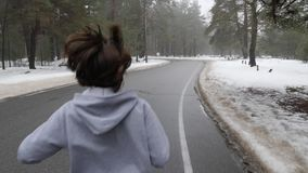 Young Attractive Caucasian girl running in the snowy park in winter with headphones. Close up Back follow shot. Slow Motion.  stock video footage