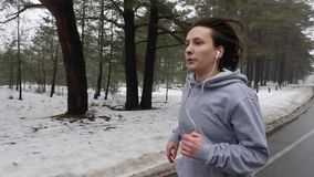 Young Attractive Caucasian girl running in the snowy park in winter with headphones. Close up Front follow shot.  stock footage