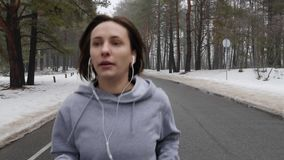 Young Attractive Caucasian girl running in the snowy park in winter with headphones. Close up Front follow shot. Slow Motion.  stock video footage