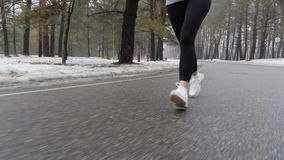 Young Attractive Caucasian girl running in the snowy park in winter with headphones. Close up legs Front follow shot.  stock video