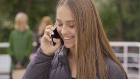 Young attractive caucasian girl talking by the phone and her friends waiting for her in the background. Leisure together. Girls spending time in the city stock video