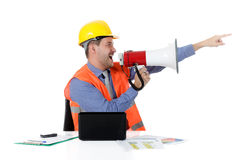 Young attractive caucasian man architect, yelling. Young attractive caucasian man architect with helmet at office with laptop, yelling at megaphone. Studio shot stock photo
