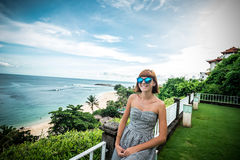 Young attractive caucasian woman with blue sunglasses near the ocean on a summer day. Amazing green and blue scene Royalty Free Stock Photography