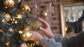 Young attractive caucasian woman decorates Christmas tree by gold balls, christmas eve, x-mas arrangements, garlands and stock video