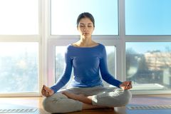 Young attractive sport girl woman doing yoga in the morning sun sitting in the Lotus position at the window. Portrait in natural l stock photo