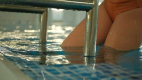 Young attractive Caucasian woman in orange swimwear exit the swimming pool by metal ladder slow motion shot.  stock footage